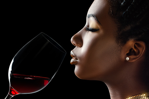 African woman smelling red wine aroma