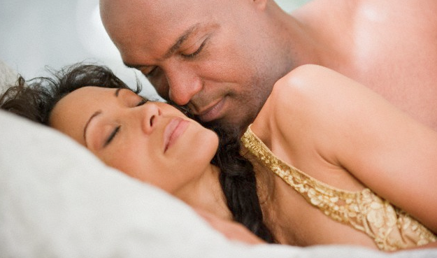 A man snuggling with a woman in bed