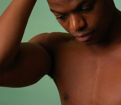 african american male on aqua background with his hands to his head.