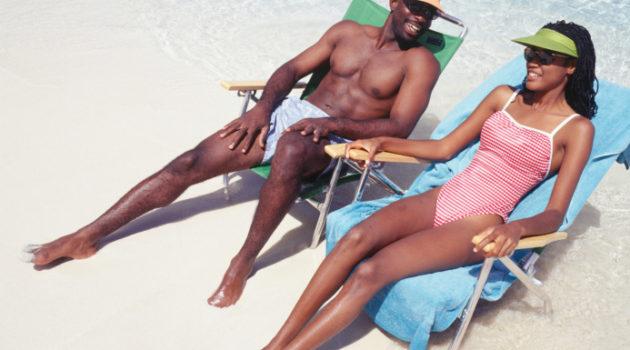 Man and woman sunbathing in deckchairs on beach