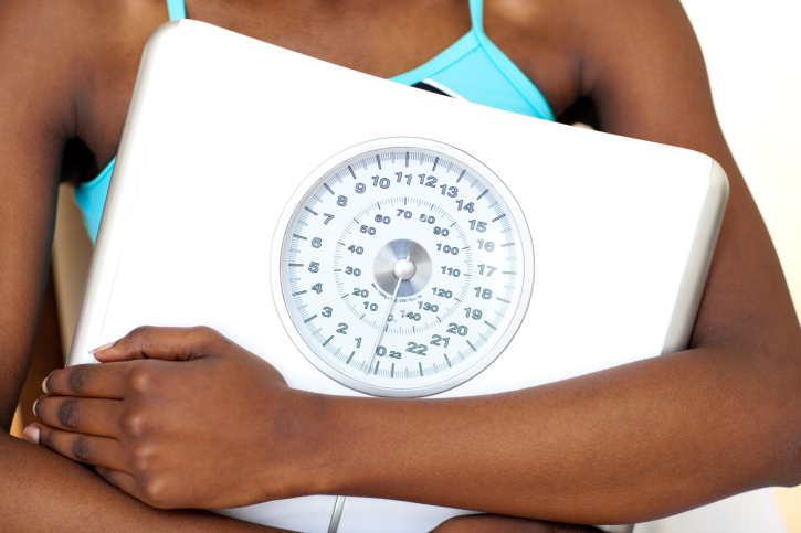 woman wearing gym clothes holding scale