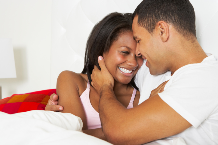 African American couple relaxing in bed