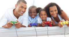 African American Black Animated family playing video game lying down on bed