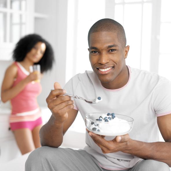 African American man eating yogurt