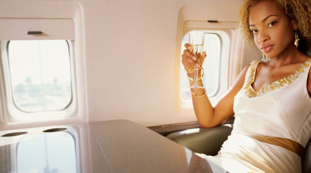 African American woman drinking champagne on plane