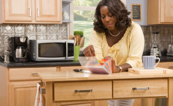 African American woman filing coupons in kitchen