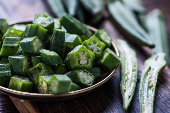 Farm fresh okra on wooden board, whole and sliced