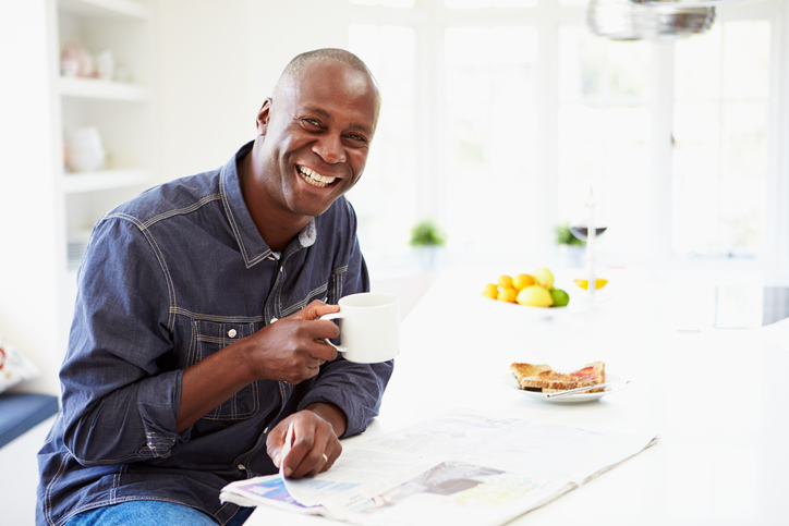 African American man eating breakfast with coffee