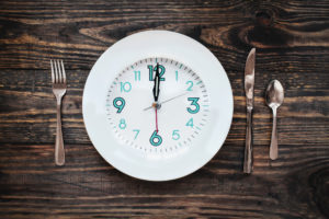 Twelve hour intermittent fasting time concept with clock on plate.