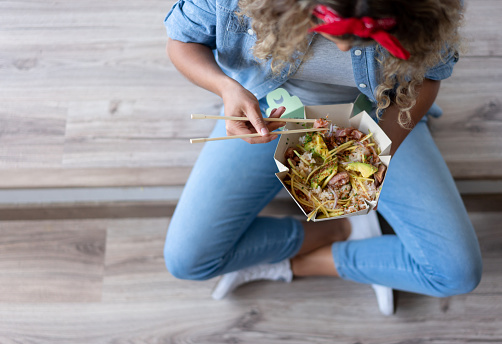 Close-up on a woman eating a poke bowl at home while moving house